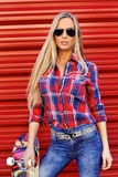 Fashionable female model in sunglasses posing on a red wall Stock Image