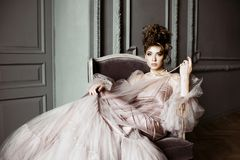 Fashionable female portrait of cute lady in pink dress indoors. Close up beautiful model girl in elegant pose. Closeup beauty blonde woman with hairstyle and royalty free stock photos