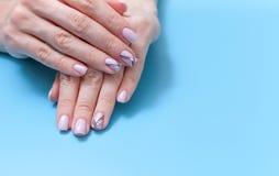 Fashionable feminine art, beautiful unique nail manicure on a blue background royalty free stock photos