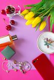 Fashionable frame. Girls stuff at pink. Copy space picture. Bright red smartphone, bouquet of yellow tulips, red raw cherries, toilet water and jewelry at violet royalty free stock image