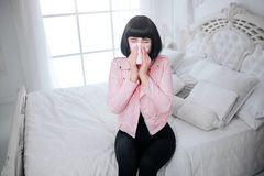 Fashionable freak. Glamour woman with short black hair is blowing nose and suffering from ill in the white bedroom stock photos