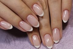 Fashionable french manicure. On beautiful female hands stock photography