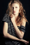Fashionable ginger model in striped t-shirt. Portrait of a fashionable ginger model in t-shirt with black and white stripes over black background. Healthy long Stock Image
