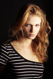 Fashionable ginger model in striped t-shirt. Portrait of a fashionable ginger model in t-shirt with black and white stripes over black background. Healthy long Stock Photo