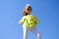 The fashionable girl. The nice girl in green clothes, white bridges and sun glasses stands against the sky in the summer Royalty Free Stock Photos