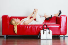 Fashionable girl with bag handbag on red couch. Elegant outfit. Female fashion. Blonde woman wearing fashionable clothes high heels with bag handbag lying on red Royalty Free Stock Photo