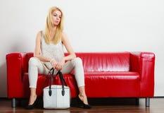 Fashionable girl with bag handbag on red couch Stock Image