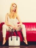 Fashionable girl with bag handbag on red couch Stock Photography