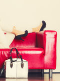 Fashionable girl with bag handbag on red couch. Elegant outfit. Female fashion. woman wearing fashionable clothes high heels with bag handbag lying on red couch Royalty Free Stock Photo