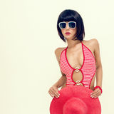 Fashionable girl in a bathing suit and hat Stock Images