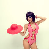 Fashionable girl in a bathing suit and hat Royalty Free Stock Image