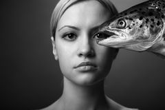 Fashionable girl with big fish. Fashionable elegant girl with big fish on dark background Stock Photos
