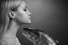 Fashionable girl with big fish stock images