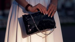 Fashionable girl with a black bag in her hands stock video