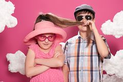 Fashionable girl and boy posing on a pink background with clouds Royalty Free Stock Photos