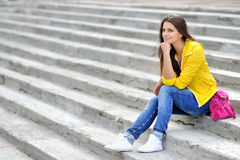 Fashionable girl in bright clothes sitting on a stairs and looki Stock Photo