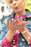 Color manicure. Fashionable girl with bright colorful nail designs blows confetti in her hands.Nails art.Color manicure stock photo