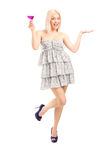 Fashionable girl with cocktail gesturing happiness Royalty Free Stock Images
