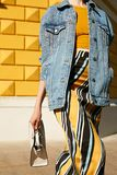Fashionable girl in a denim jacket, yellow top and in a skirt with an ornament in a hurry, waving a white square bag. Street lifes royalty free stock images