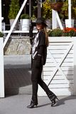 Fashionable girl dressed in black trousers, a stylish gray shirt and sweater and in a black hat with wide brim walks in royalty free stock photos