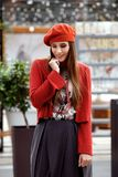 Fashionable girl dressed in a gray skirt, a red blouse on the t-shirt and red beret poses in the street on the sunny day stock images