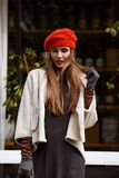 Fashionable girl dressed in stylish gray dress, short sheepskin coat, gloves and red beret walks in the park on the stock image