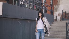 The fashionable girl goes down the stairs. Portrait of an attractive girl on a background of architecture. a young woman. Portrait of a fashionable girl on the stock footage