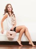 Fashionable girl with handbag sitting on sofa Stock Images