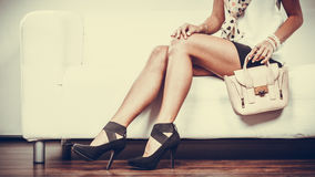 Fashionable girl with handbag sitting on sofa Royalty Free Stock Image