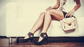 Fashionable girl with handbag sitting on sofa Royalty Free Stock Image