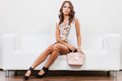 Fashionable girl with handbag sitting on sofa Stock Image