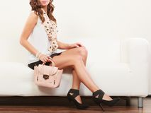 Fashionable girl with handbag sitting on sofa Stock Photo