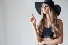 Fashionable girl in a hat with a brim poses for advertising. 1 royalty free stock photo
