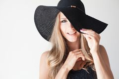 Fashionable girl in a hat with a brim poses for advertising. 1 royalty free stock image
