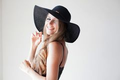 Fashionable girl in a hat with a brim poses for advertising. 1 royalty free stock photography