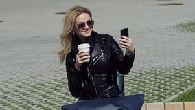 Fashionable girl in leather jacket taking a selfie on smartphone. Fashionable girl in leather jacket taking selfie on smartphone stock footage