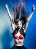 Fashionable girl with long hair jumping in fur waistcoat and red bra. Stock Images