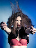 Fashionable girl with long hair jumping in fur waistcoat and red bra. Royalty Free Stock Image