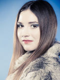 Fashionable girl with long hair. Young woman in fur coat on blue. Royalty Free Stock Photography