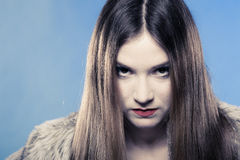 Fashionable girl with long hair. Young woman in fur coat on blue. Royalty Free Stock Image