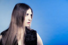 Fashionable girl with long hair. Young woman in fur waistcoat. Stock Photography