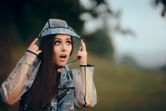 Surprised Woman in Clear Transparent Raincoat in Summer Rain. Fashionable girl outdoors in nature in rainy weather Stock Photo