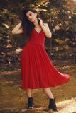 Fashionable girl in park or forest. Hipster woman with a fashionable red long dress.   Brunette beauty model. Girl with red lips stock image