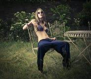 Fashionable girl posing in a garden Royalty Free Stock Photos