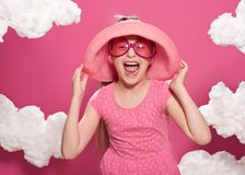 Fashionable girl posing on a pink background with clouds, pink dress and hat Stock Images