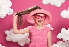 Fashionable girl posing on a pink background with clouds, pink dress and hat Stock Photo