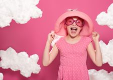 Fashionable girl posing on a pink background with clouds, pink dress and hat Royalty Free Stock Images