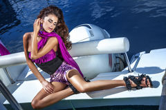 Fashionable girl posing on the yacht. Fashionable photo of beautiful brunette woman posing on the yacht Royalty Free Stock Photography