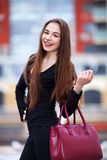 Fashionable girl in red dress with bag crossing a city street Stock Photography