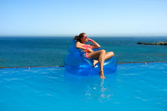 Fashionable Girl Relaxing in the Pool. Summer Vacation. Beautiful young woman sitting on inflatable chair sunbathing. Relax in swimming pool with wonderful sea Stock Photos